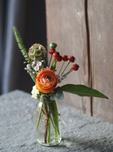 Oreonta house woodstock wedding bud vase with orange ranunculous, lambs ears, grey brunia, red berries and red rosehips and wildflowers rosehip social rosehip floral pink wax flowers