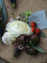 Oreonta house woodstock wedding corsage with white ranunculus eucaliptus seed podds and orange rosehip berries